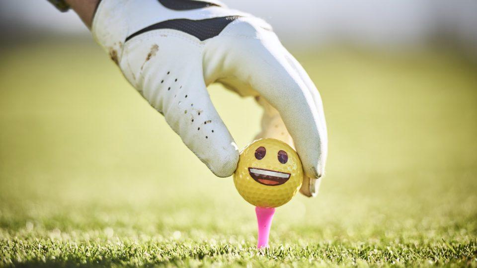 yellow smiley face golf ball on tee